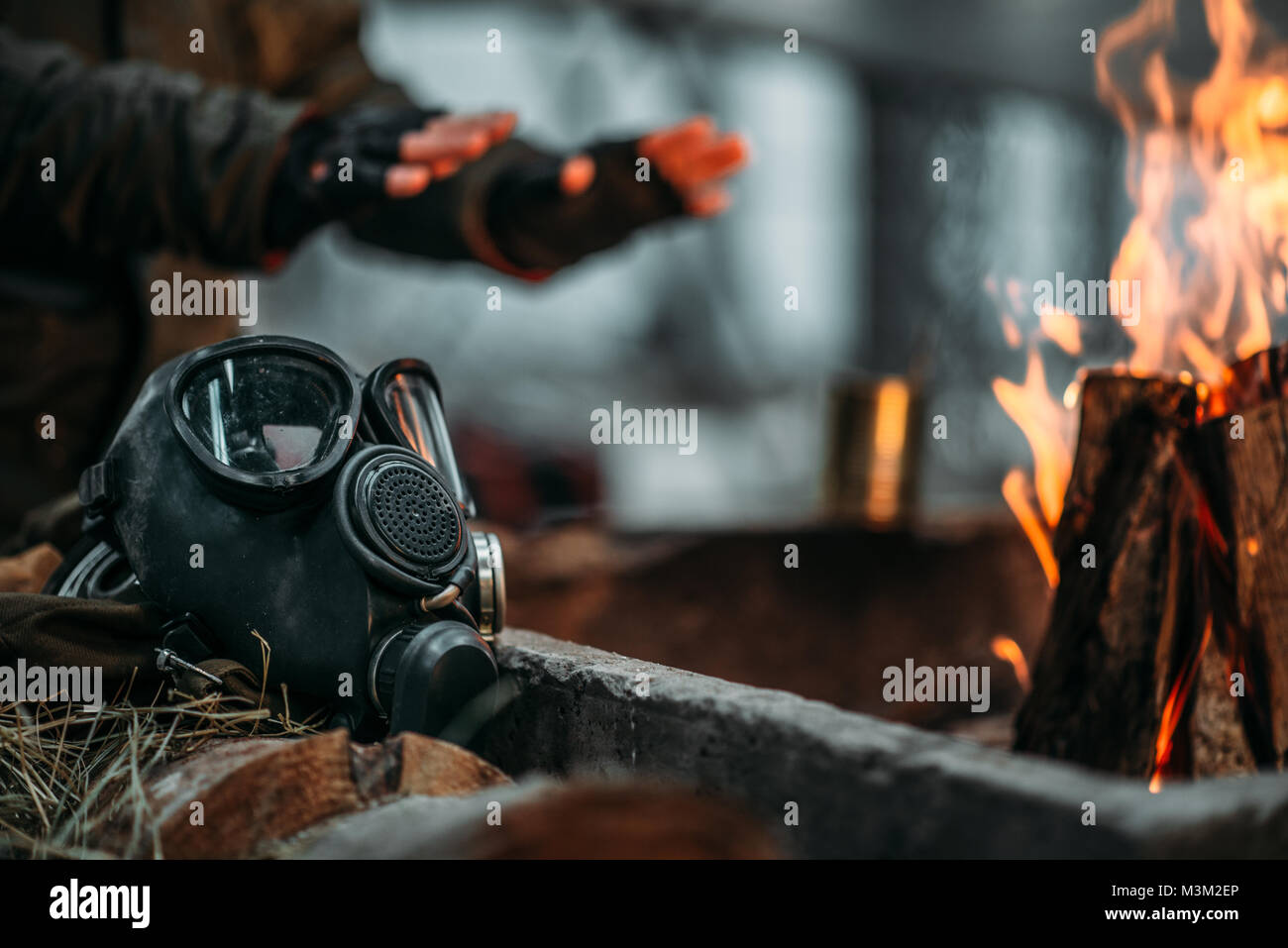Stalker, male person warms his hands on fire. Post apocalyptic lifestyle with gas mask, doomsday, Stock Photo