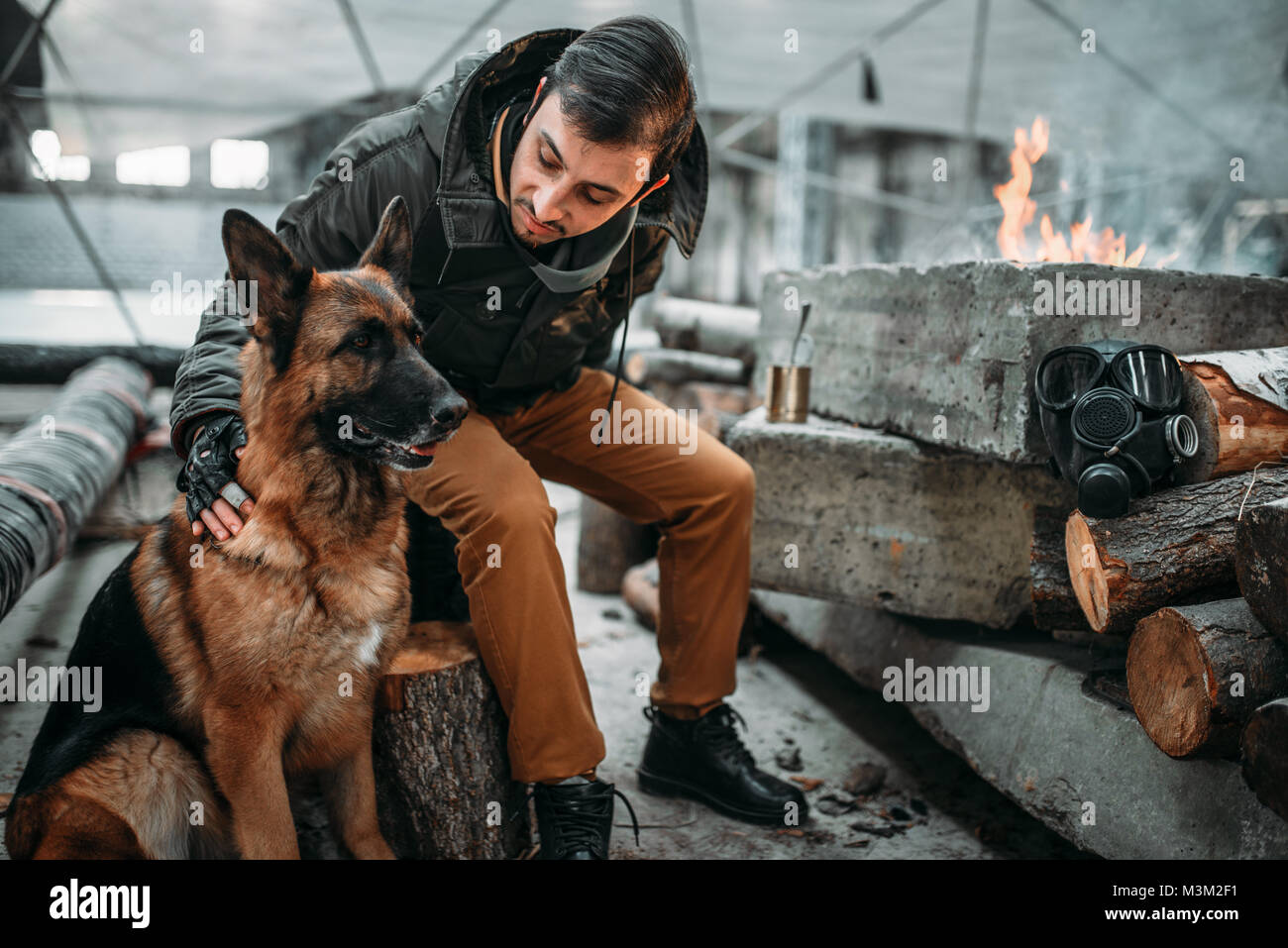 Stalker, post-apocalypse soldier feeding a dog. Post apocalyptic lifestyle on ruins, doomsday, judgment day - Stock Image
