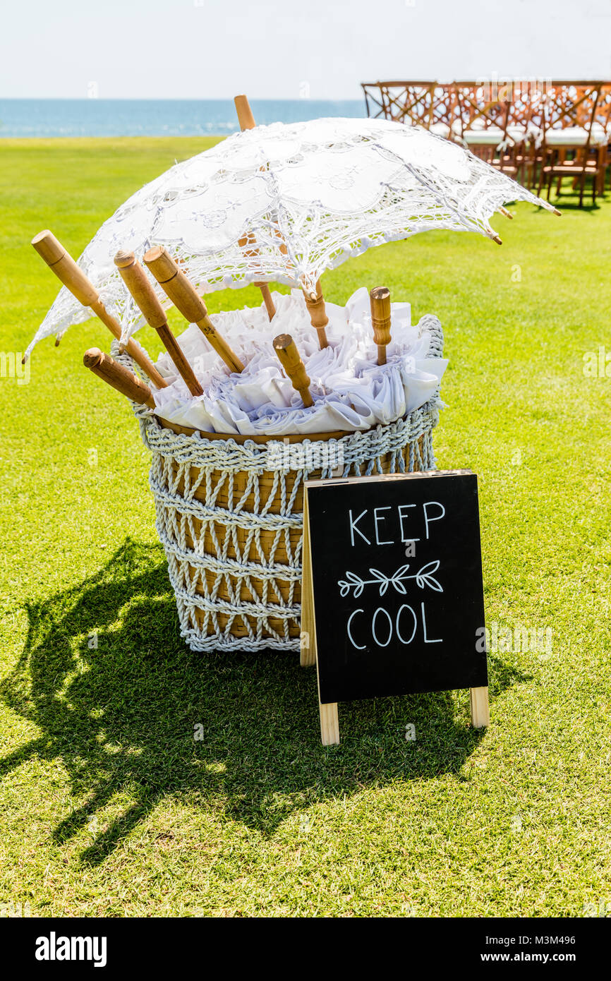 Wedding setup - white parasols for guests in a basket and a sigh KEEP COOL, Bali, Indonesia. Vertical image. - Stock Image