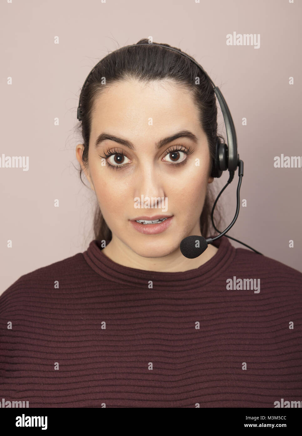 Call center operator with a surprised expression listening to a conversation on her headset and staring wide eyed Stock Photo