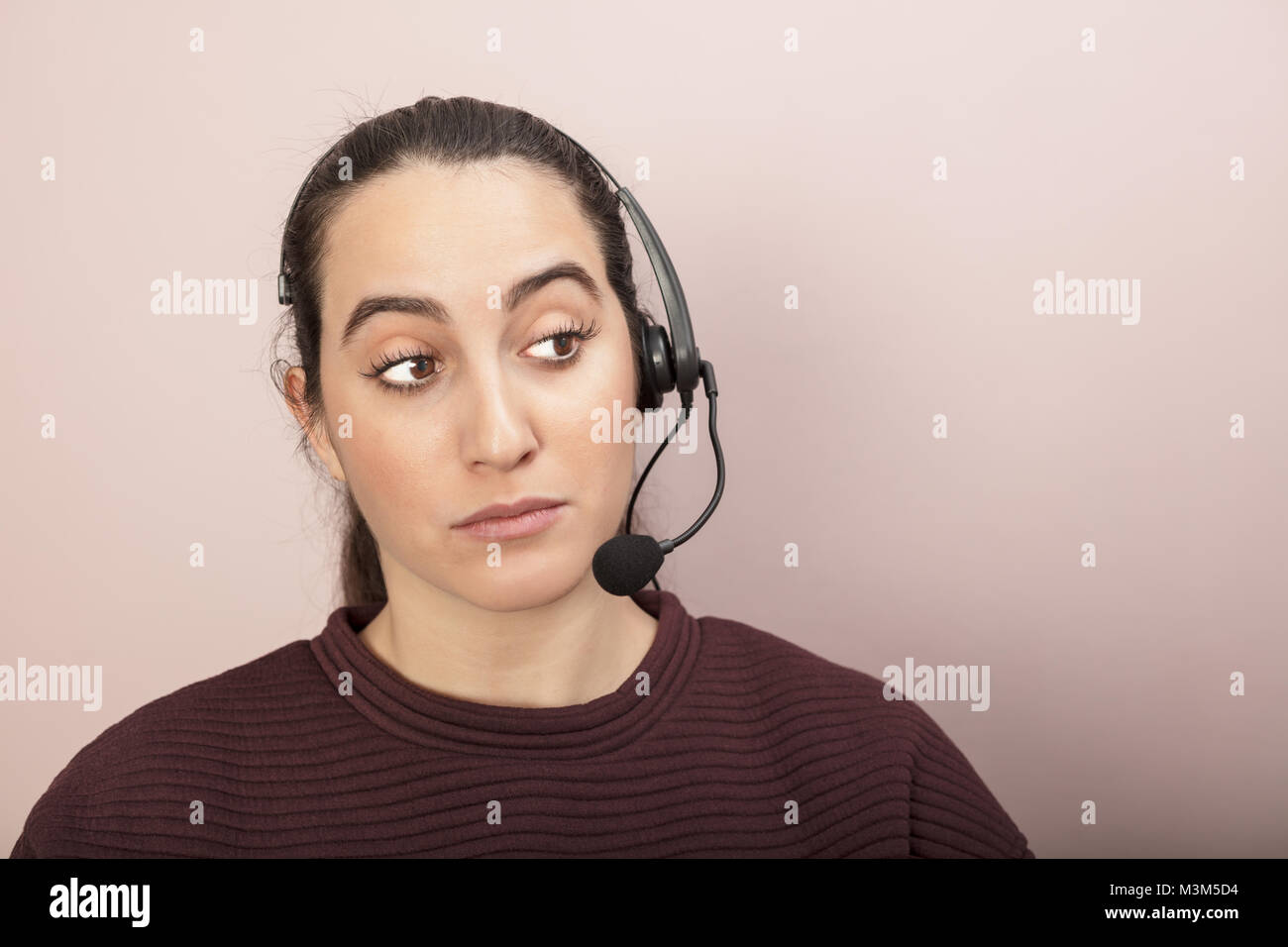 Sceptical help desk or call center operator listening to a call looking to the side with raised eyebrows and a dubious - Stock Image
