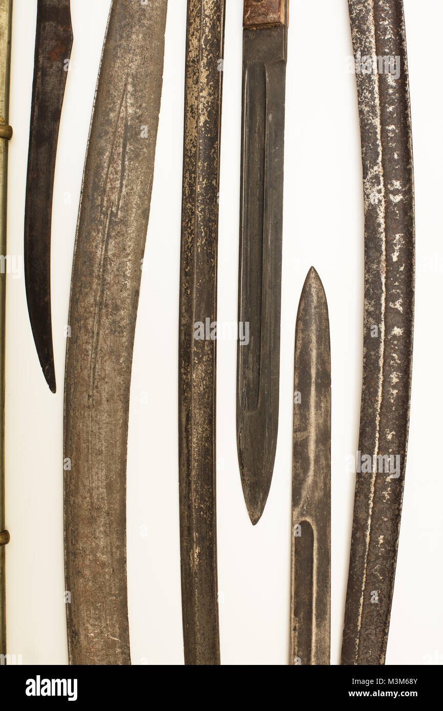 Display case with old historical swords and knives on a white background in an exhibit in a museum or collectors - Stock Image