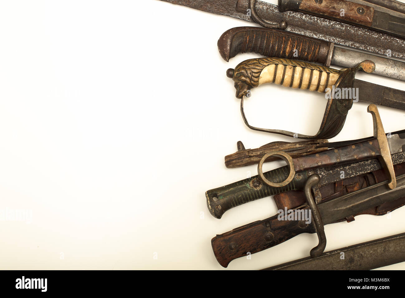 Collection of vintage weapons with the hilts of old swords and daggers forming a side border over white with copy - Stock Image