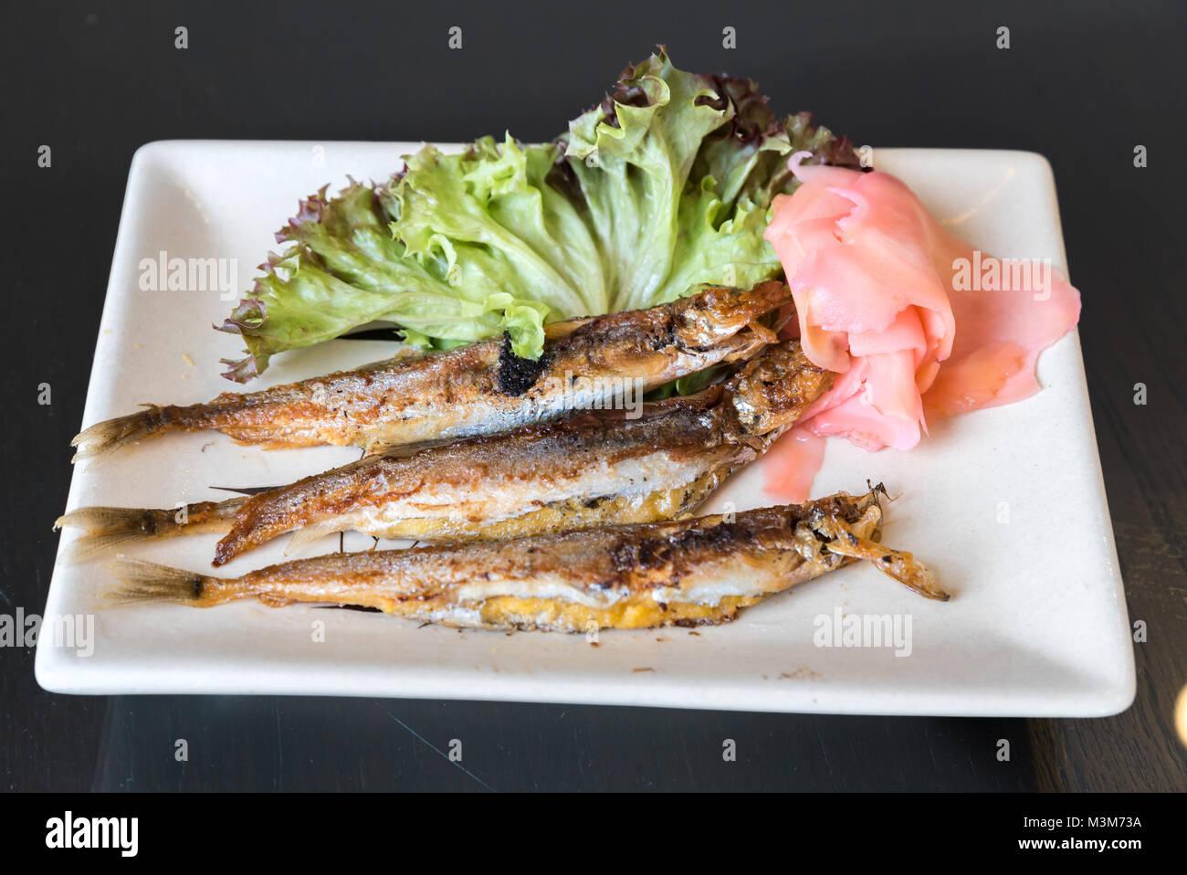 grilled shishamo on white plate - Stock Image
