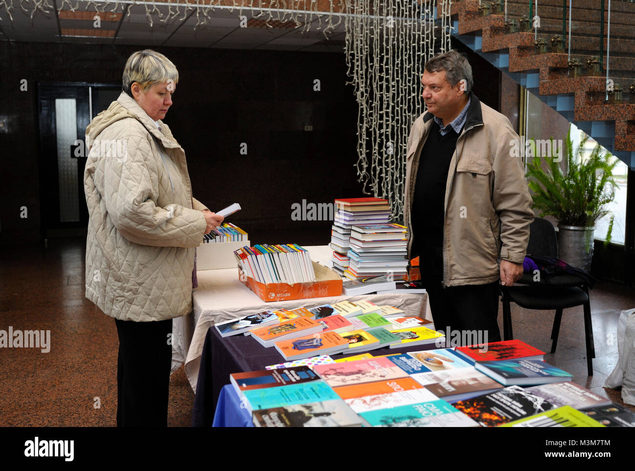 """Bookseller tells visitor about books available at his bookshop. Book Fair """"Book contracts"""". December 14, 2017. Kiev, - Stock Image"""