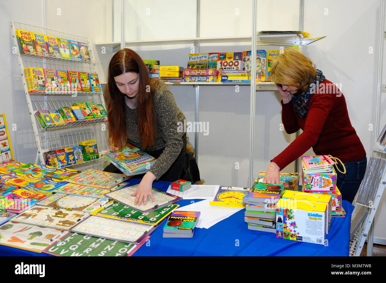 """Bookseller places books on bookshelves before opening a bookshop. Book Fair """"Book contracts"""". December 14, 2017. - Stock Image"""