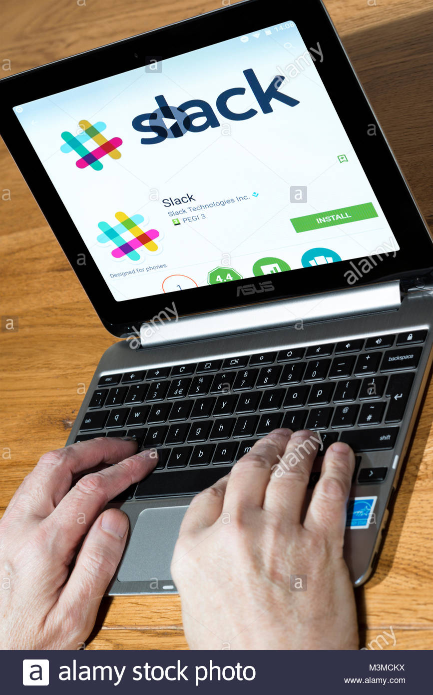 Man using an Asus Chromebook with the Slack app on the screen - Stock Image