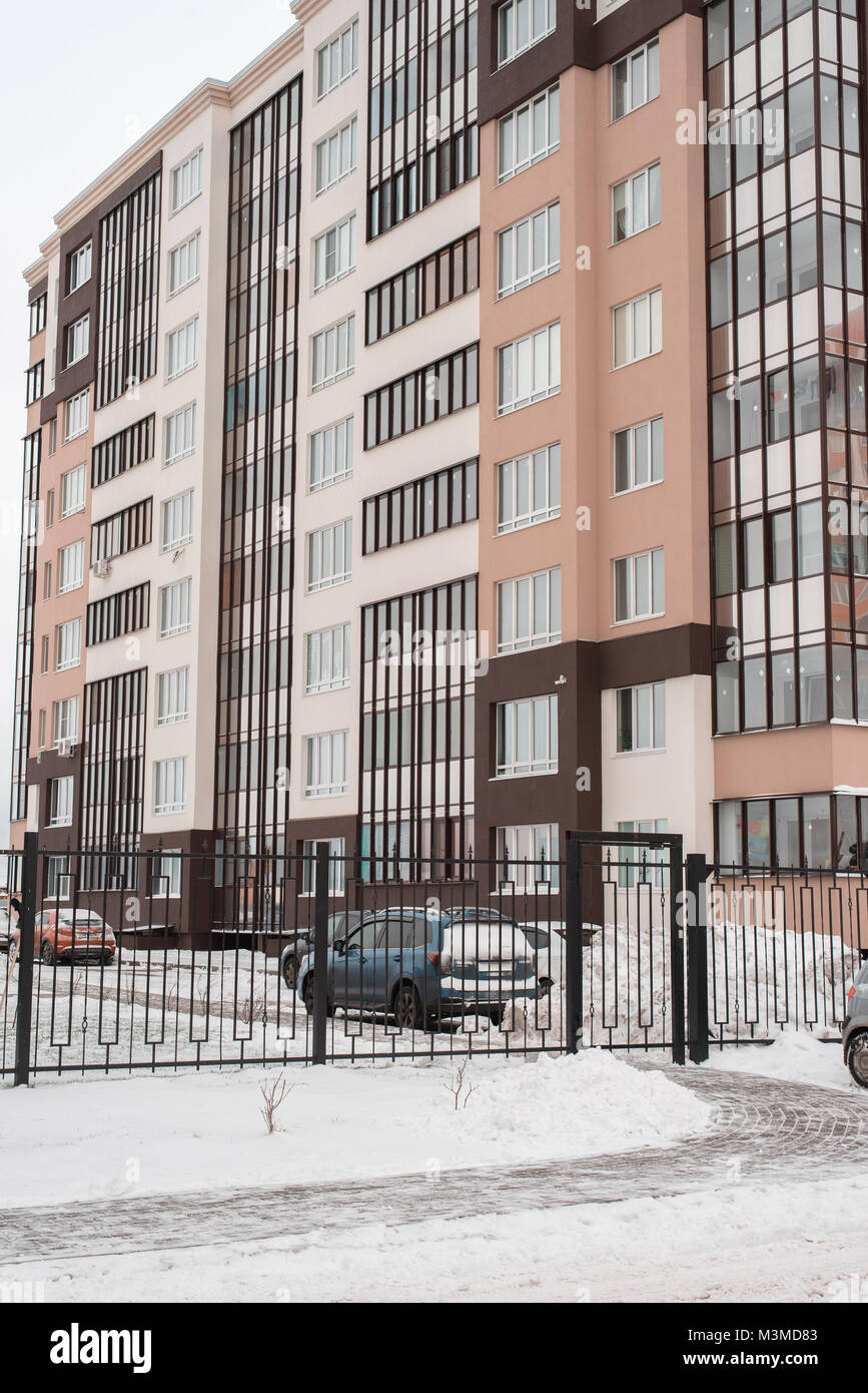 A panel house in winter, a multi-story building in a new microdistrict. Parked cars at the fence in the snow. - Stock Image