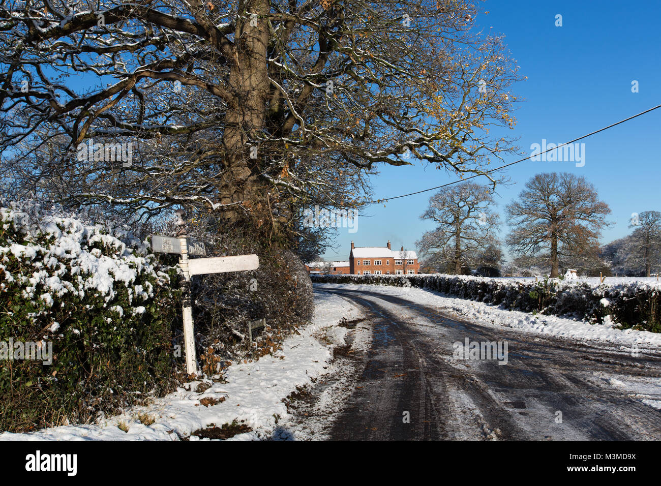 Village of Coddington, England. Picturesque winter view of a rural non-gritted road, in rural Cheshire. - Stock Image