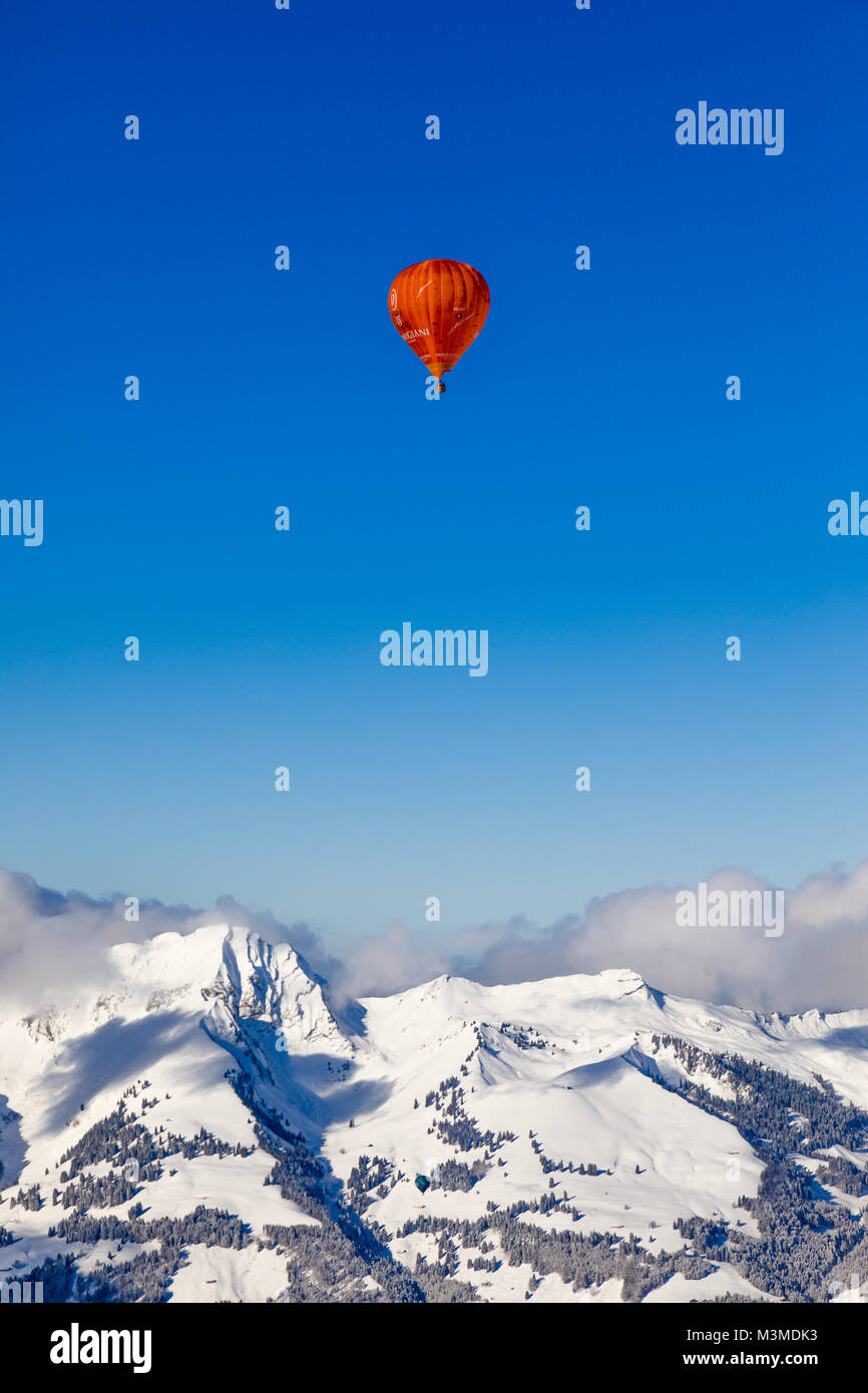 40th International Hot Air Balloon Festival in Château-d´Oex - balloons are flying in the blue sky over the swiss mountain scenery Stock Photo