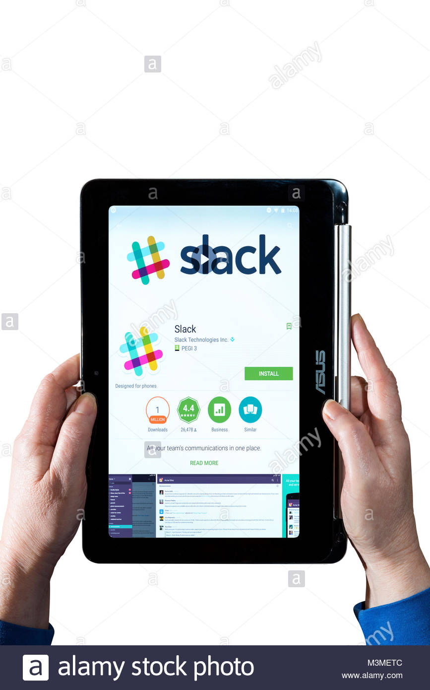 Man holding an Asus Chromebook with the Slack app on the screen - Stock Image