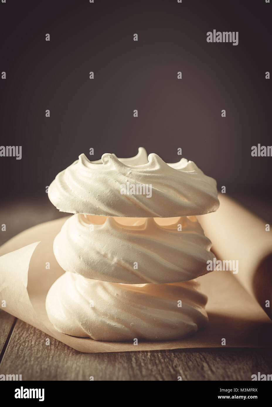 Stack of three meringue nests on parchment roll on table - Stock Image