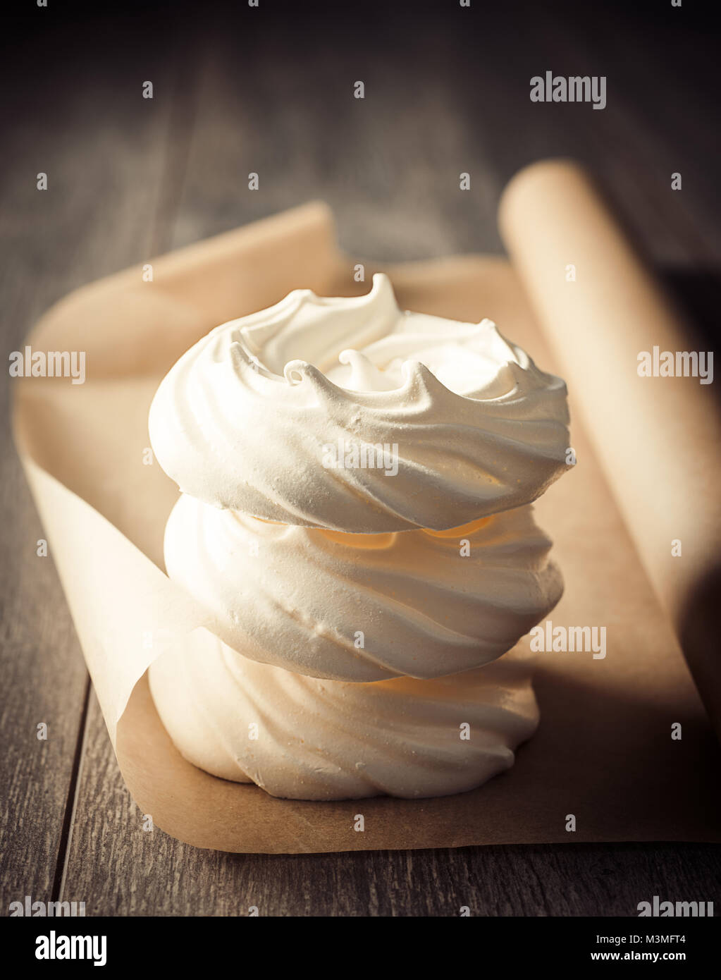 Stack of three meringue nests on parchment paper fresh out of the oven - Stock Image