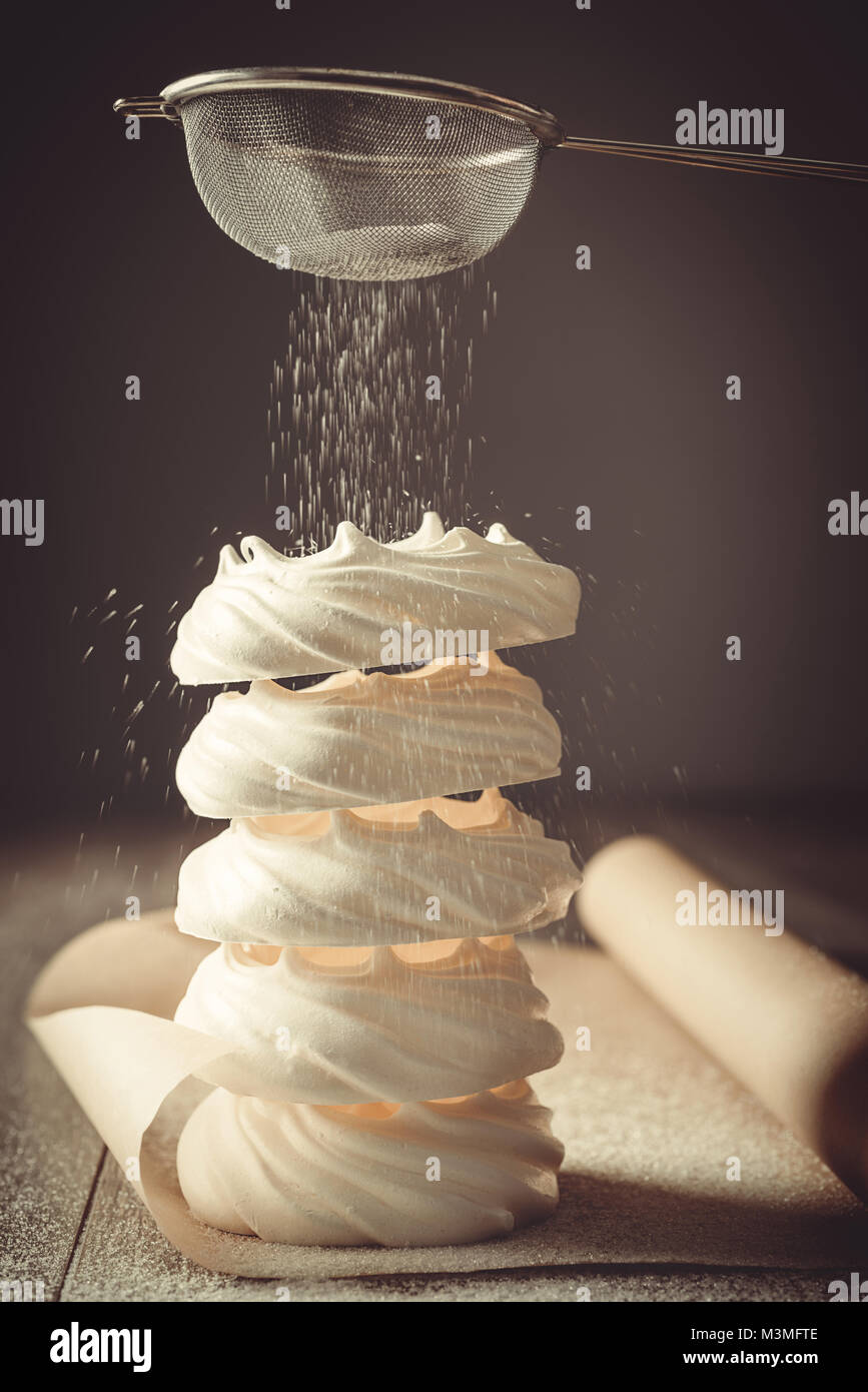 Stack of meringue nests being dusted with sugar from a sieve - Stock Image