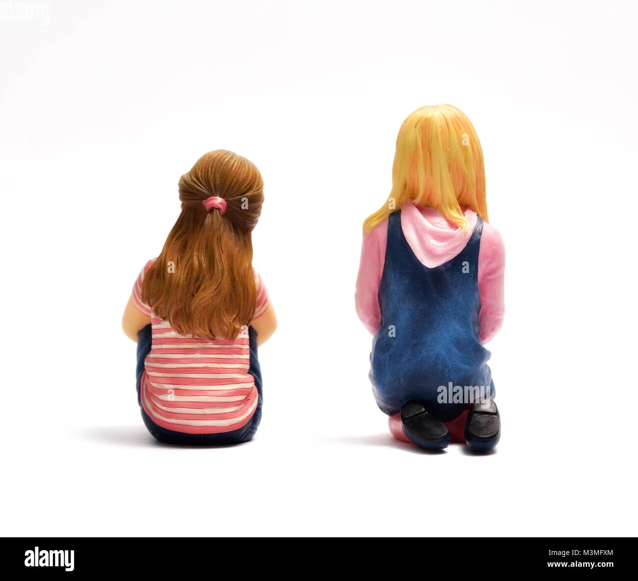Two miniature figurine girls facing forward - Stock Image