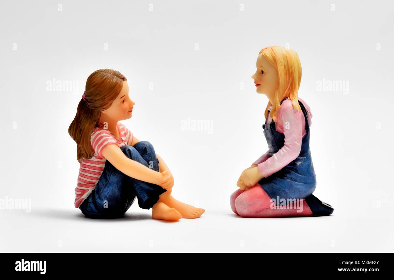 Two miniature figurine girls facing each other - Stock Image