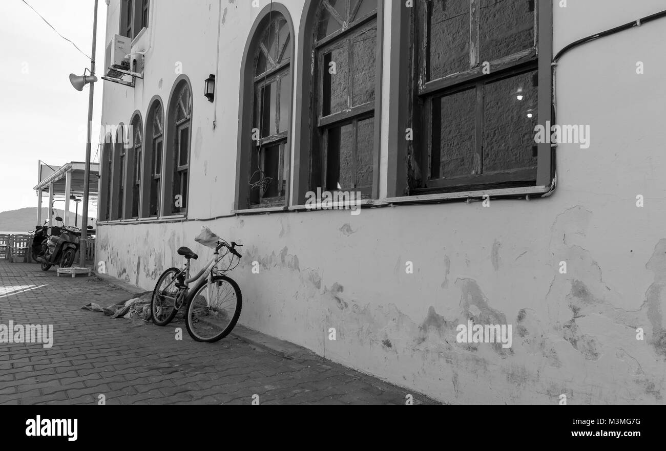 Bicycle at the old building wall. Black and white photo - Stock Image
