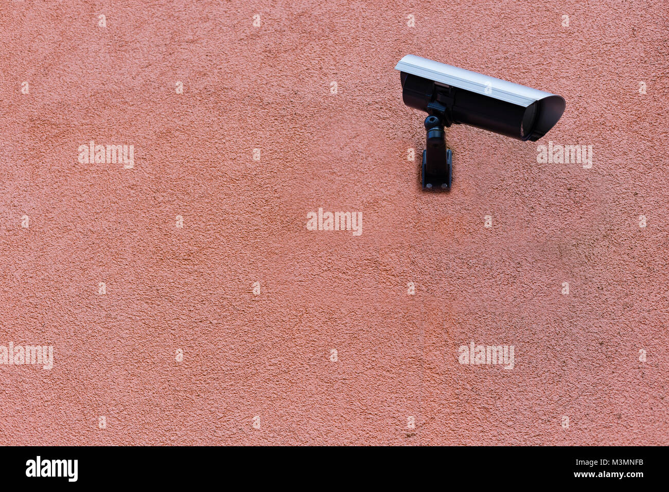 Surveillance observing camera on a orange red wall in Karlsruhe, Germany - Stock Image