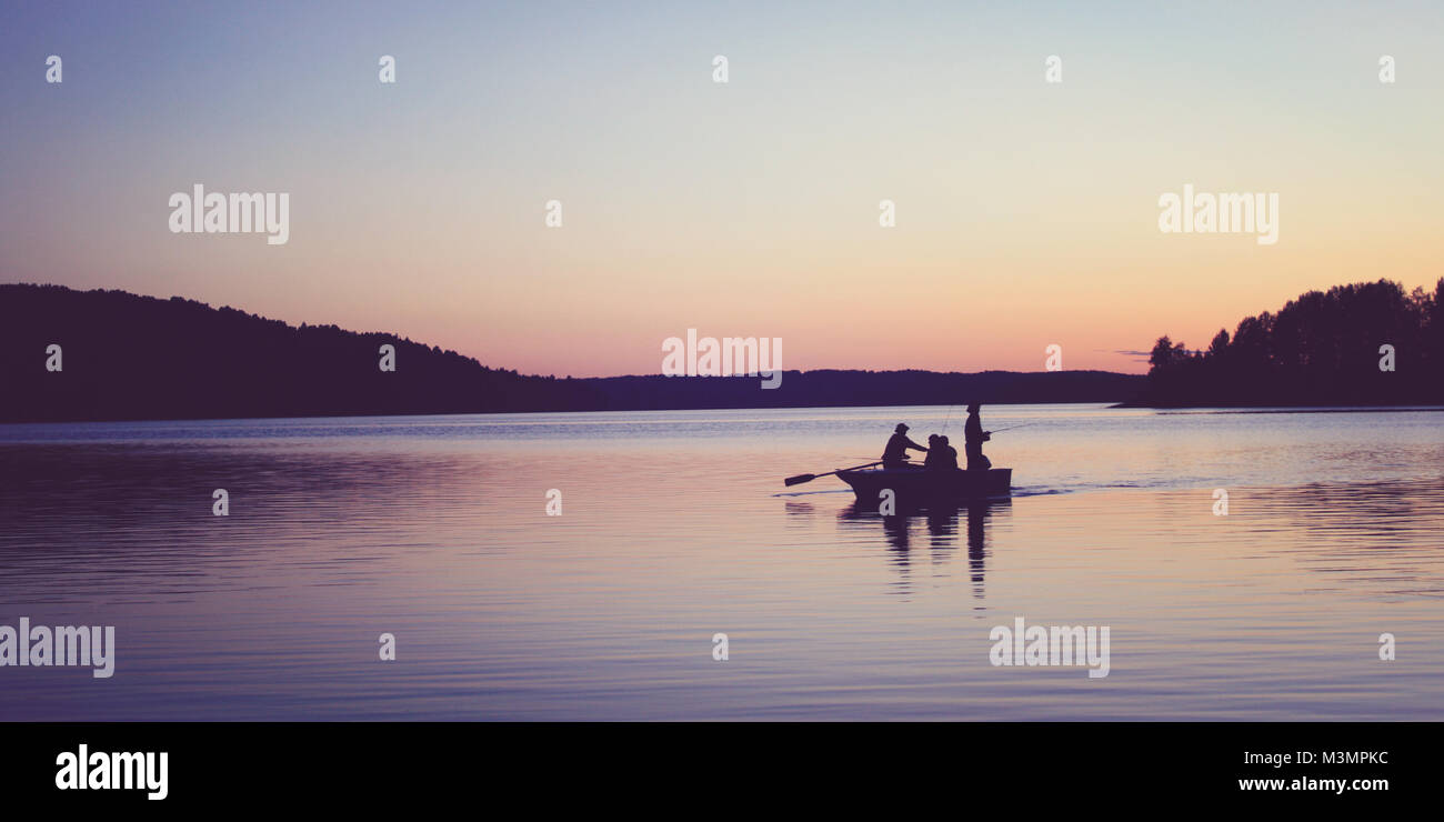 The boat with fishermen. Toned photo. Late evening on the Kenozero lake. Sunset. White nights on the north of Russia. - Stock Image