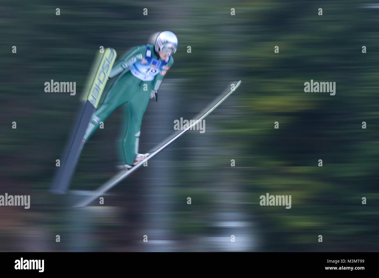 Ski jumper soars with speed in motion blur trough the air. Jumping Hill Ljubno ob Savinji, Slovenia. 27. januar - Stock Image