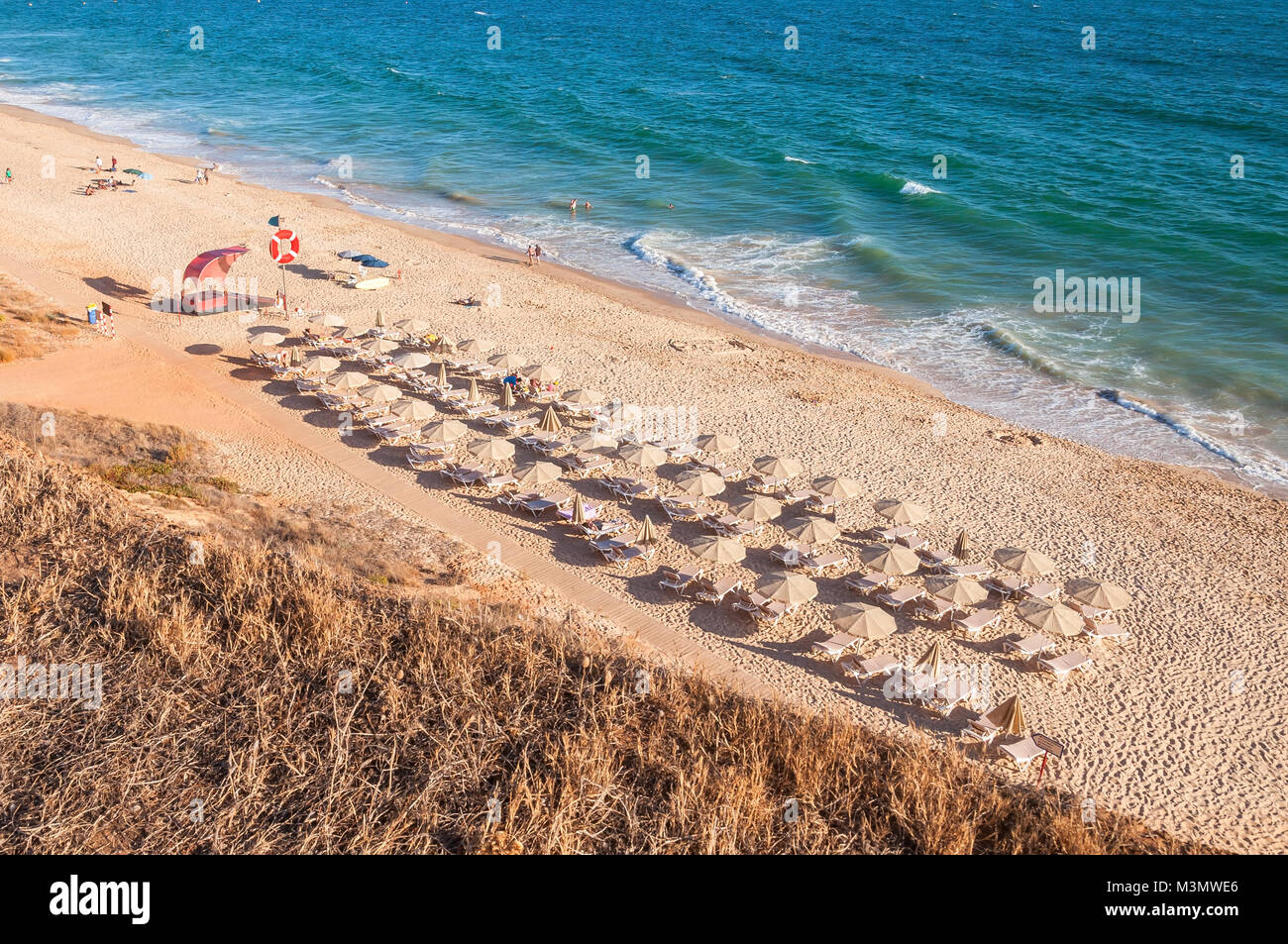 Sunbeds and umbrellas on the Falesia Beach in afternoon sun, Algarve, Portugal Stock Photo
