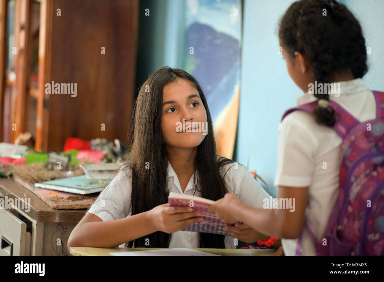 Young Maleku girls exchange an exercise book in their village school in the Maleku indian reservation, Tonjibe, - Stock Image