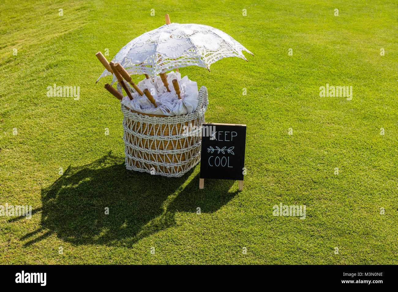 Wedding setup - white parasols for guests in a basket and a sigh KEEP COOL, Bali, Indonesia - Stock Image