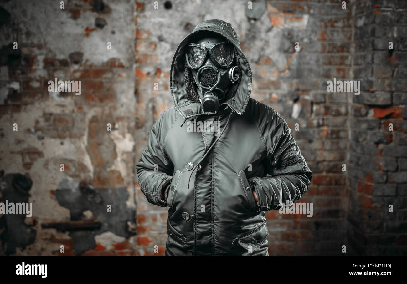Stalker soldier in gas mask, survivor man after nuclear war. Post apocalyptic lifestyle, doomsday, horror of radiation - Stock Image