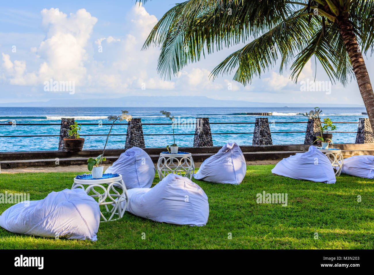 Wedding reception setup near the ocean at sunset - white bean bags for guests and rattan tables - Stock Image