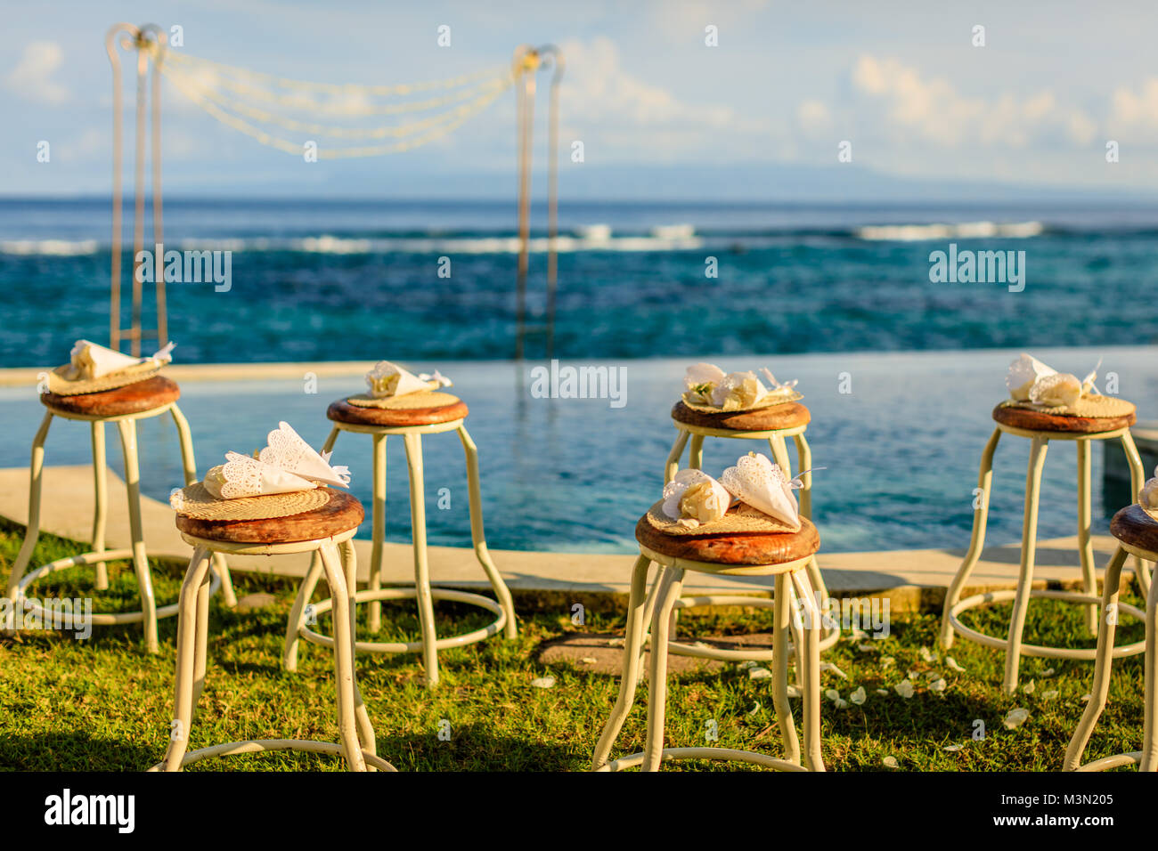 ab36ccad9f48c Wedding ceremony setup near the ocean at sunset - chairs for guests with  flower petals and