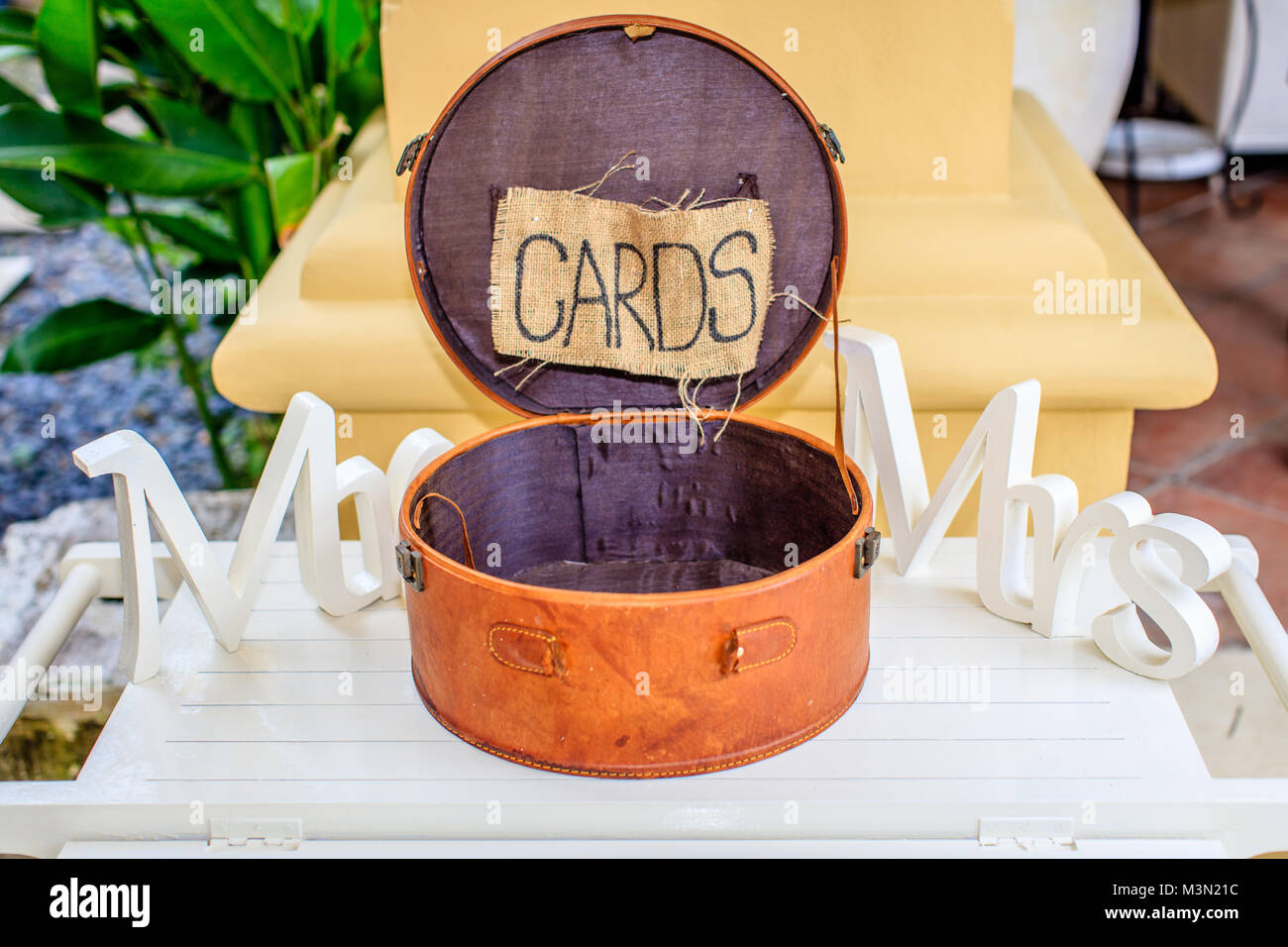 Round brown leather box for cards, white wooden words Mr and Mrs on the sides. Wedding props. - Stock Image