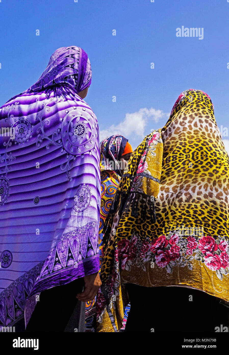 Colorful hijabs worn by three Muslim women in Zanzibar's Stone Town. - Stock Image