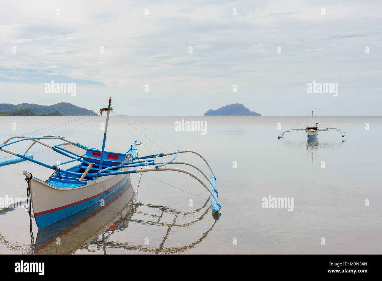 Filipino fisherman boats with traditional  outriggers float anchored in a still calm sea of Coron Bay, Palawan, - Stock Image