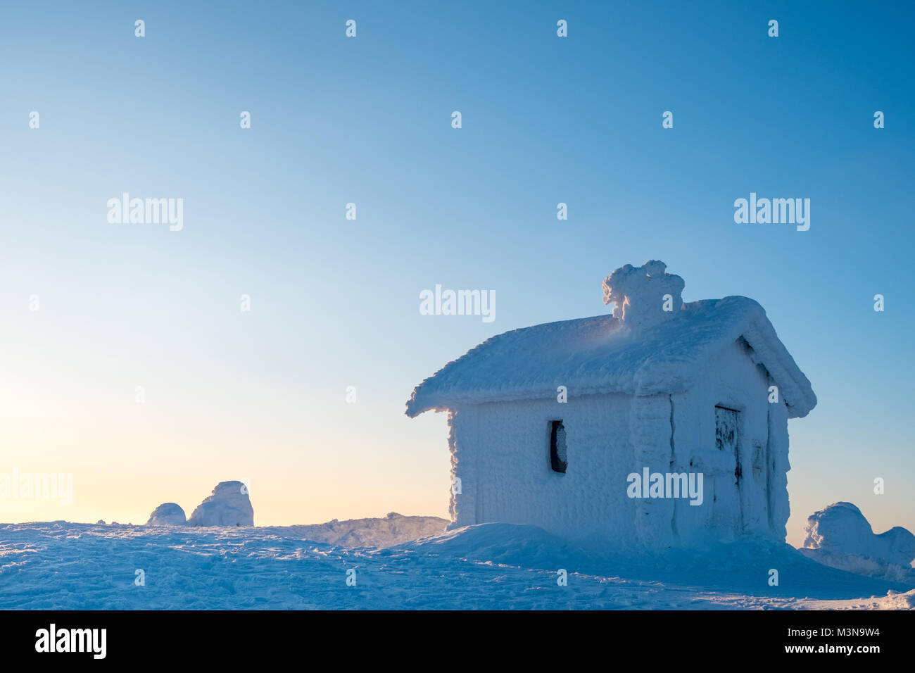 A snow encrusted cabin on the summit of a hill in Finland - Stock Image