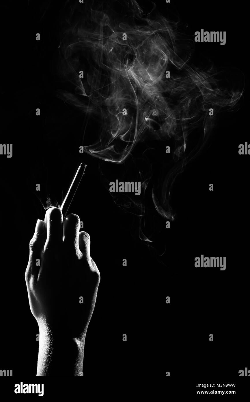 hand with burning cigarette and smoke on black background, monochrome - Stock Image