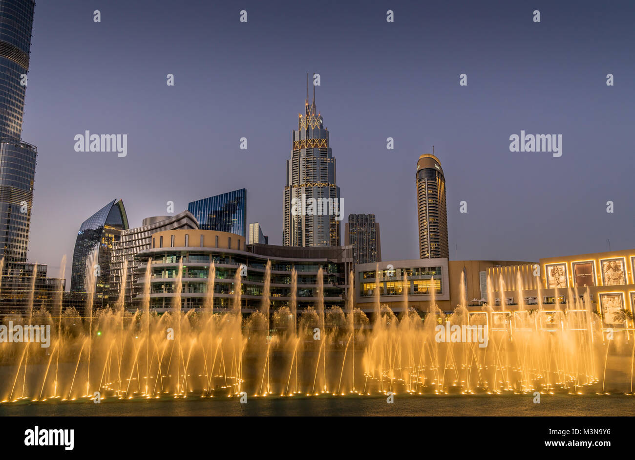 Dubai, UAE - Jan 9, 2018. Evening view of Dubai Fountain's dancing waters performance accompanied by colorful syncing Stock Photo