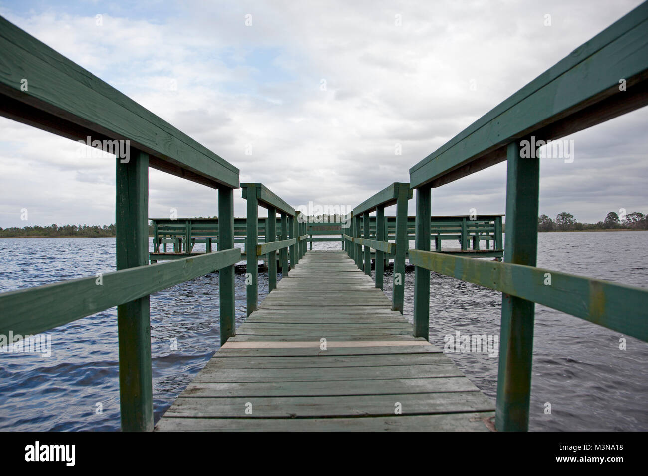 a beautiful Florida day with blue sky by a green wooden wharf at Old Lake Davenport, Florida - Stock Image