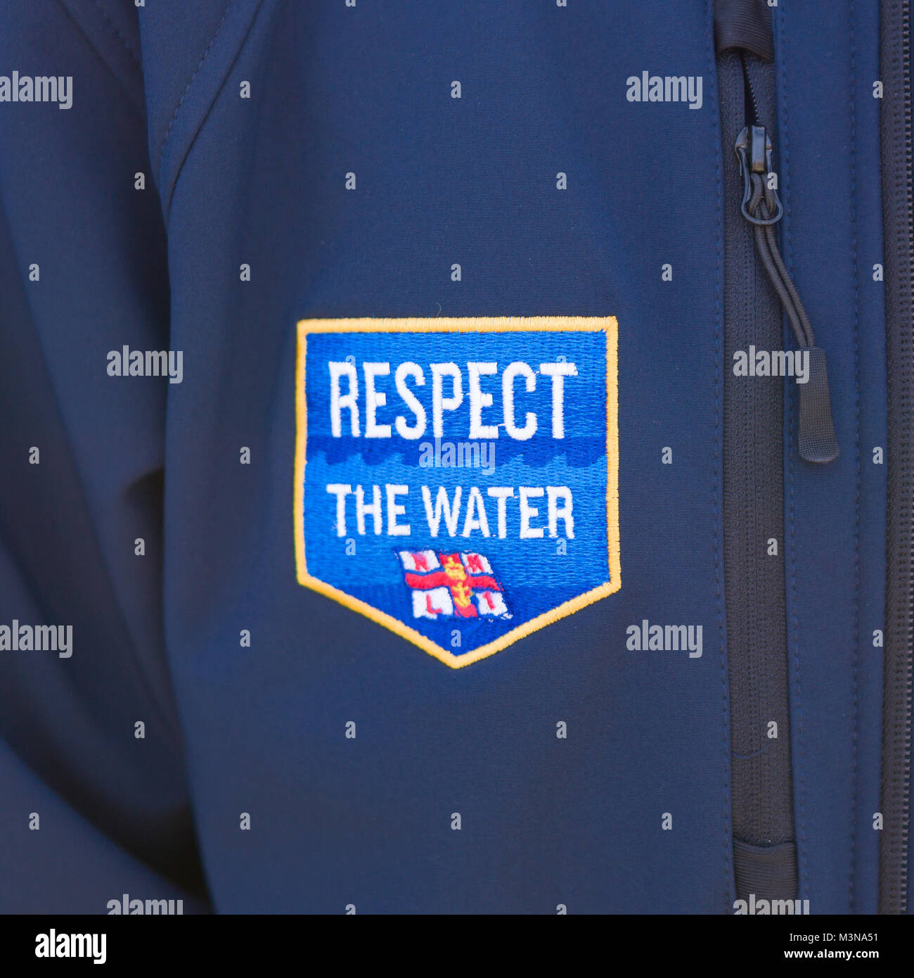 A close up of an RNLI Respect The Water patch on a blue fleece jacket. - Stock Image