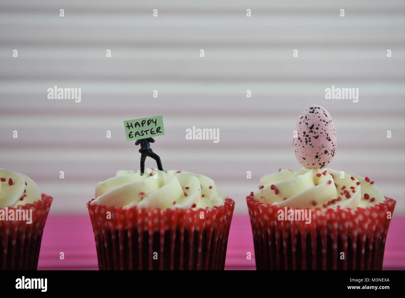 Easter time food cupcakes with miniature person figurine and sign board for happy Easter Stock Photo