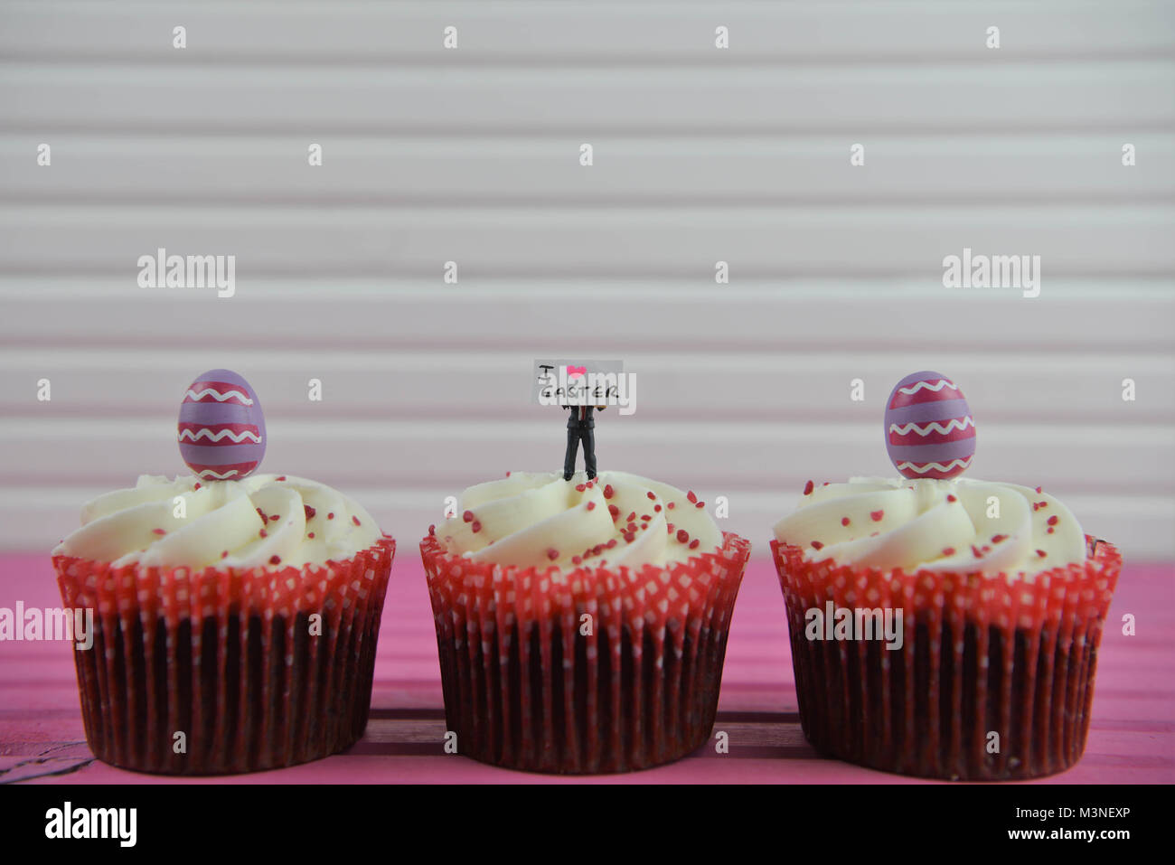 Easter time with cupcakes topped with miniature person figurine holding a sign for I love Easter Stock Photo