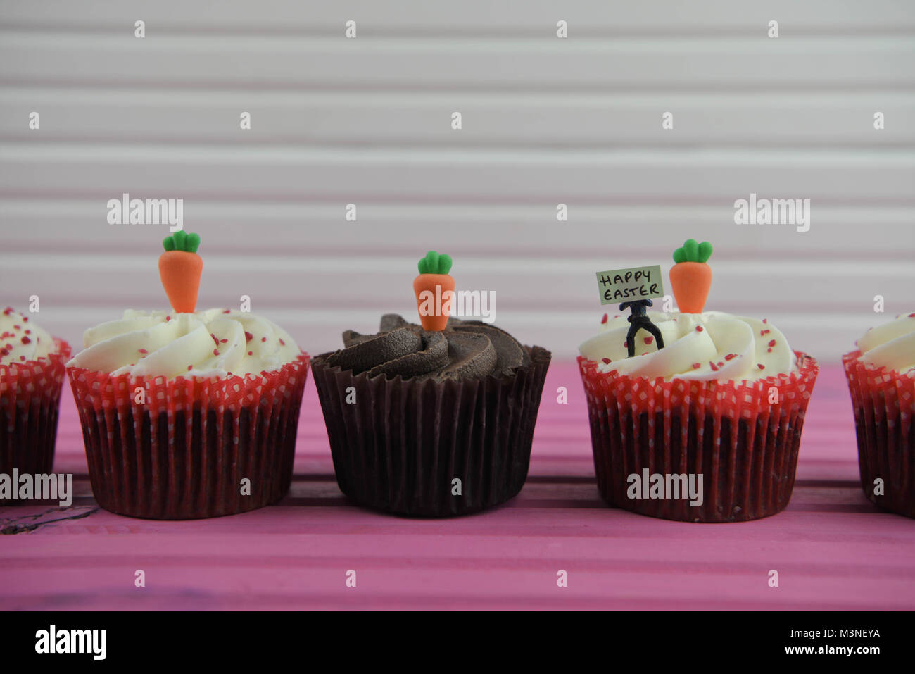 delicious Easter time cupcakes topped with miniature person figurine with sign board with I love Easter Stock Photo