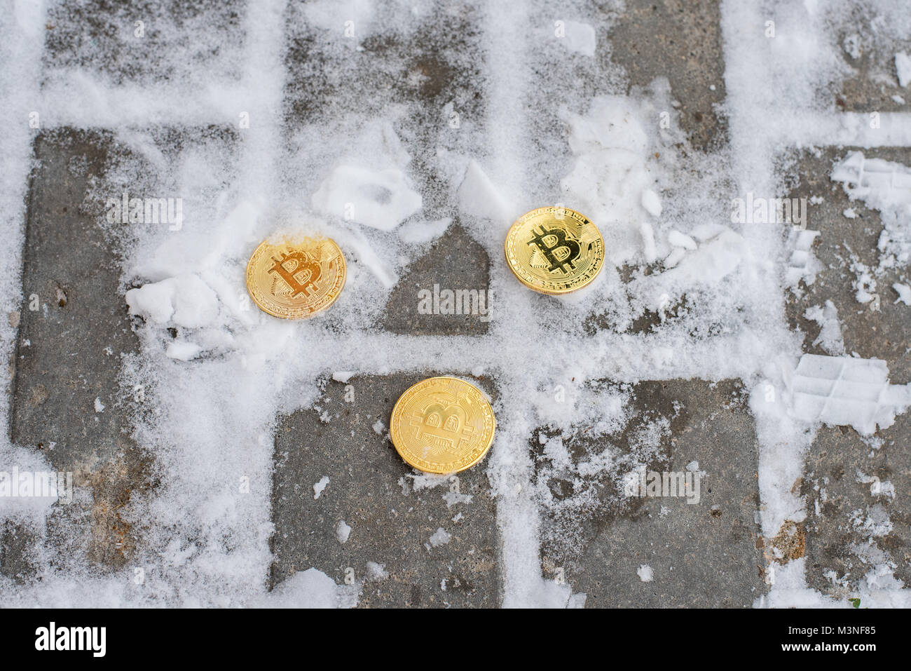 Crypto currency bitcoin, gold coins lie on asphalt in winter in white snow. Lost money on the street. - Stock Image