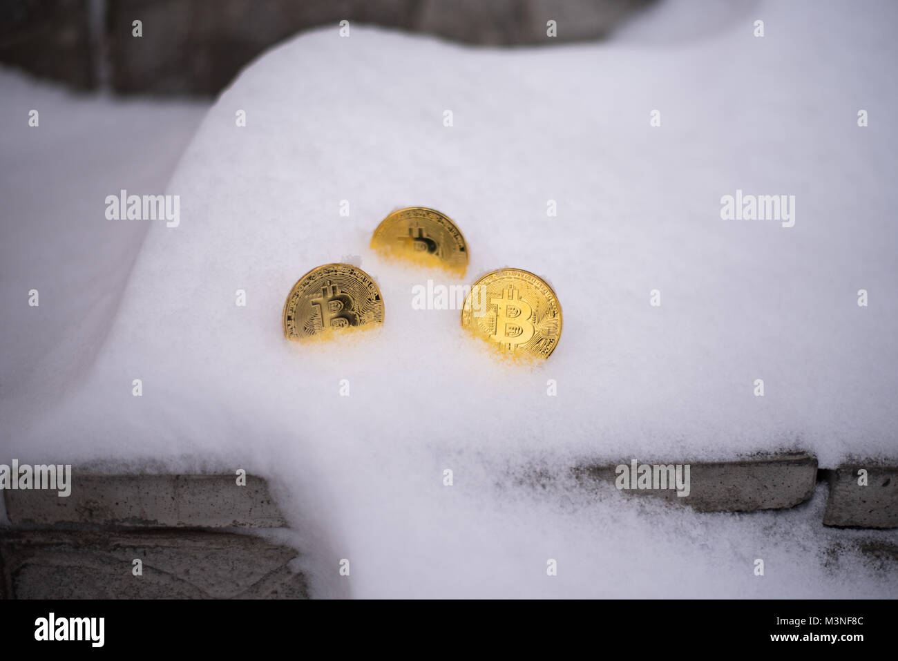 Gold coins bitcoin, crypto-currency in winter, lies in a white snowdrift, on the street. The lost money. Abandoned - Stock Image