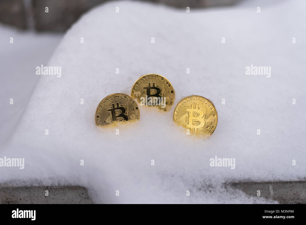Gold coins bitcoin, crypto-currency in winter, lies a white snowdrift, on the street. The lost money. Abandoned - Stock Image