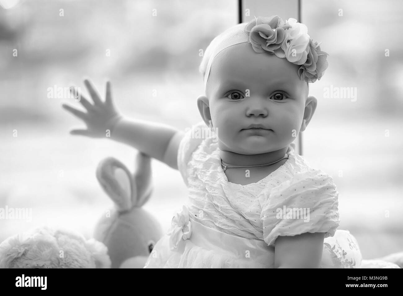 Child in the children's room. The kid is sitting on the windowsi - Stock Image