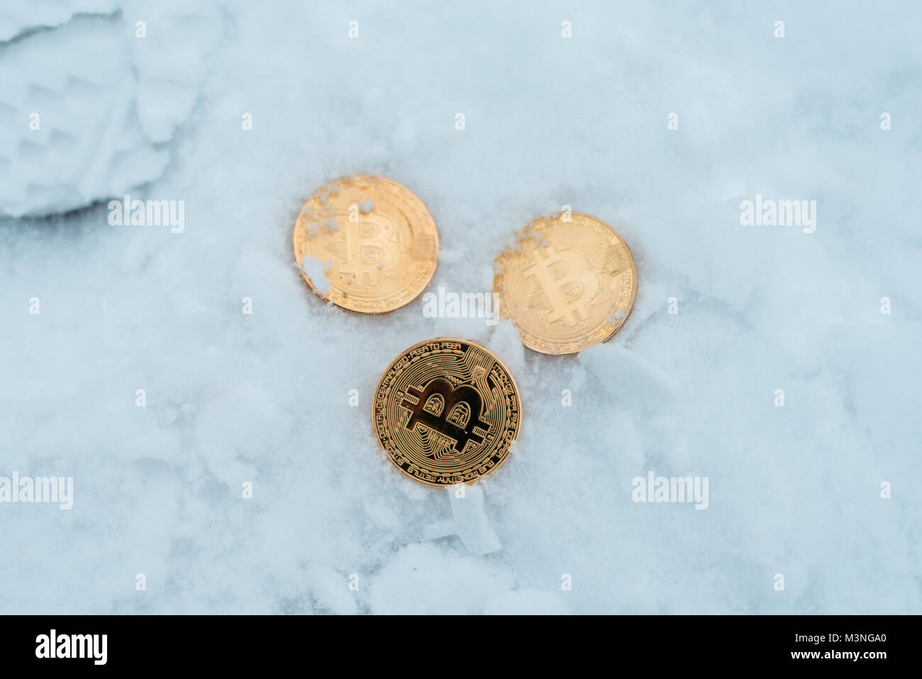 Metal gold coins bitcoin, crypto currency in winter on snow lie in snowdrift. Loss of money. - Stock Image