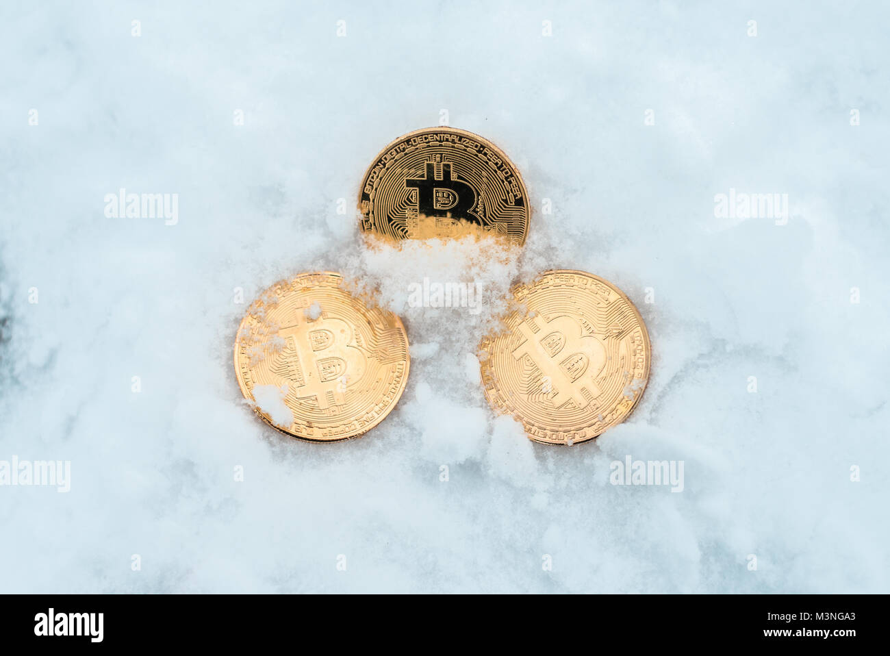 Discarded money. Metal gold coins bitcoin, crypto currency money in winter on snow lie in snowdrift. - Stock Image