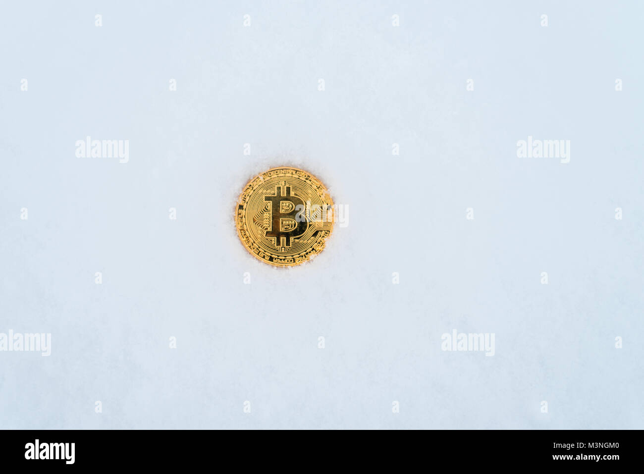The lost coin of crypto-currency in winter in the snow. Gold bitcoin in the snow alone. - Stock Image