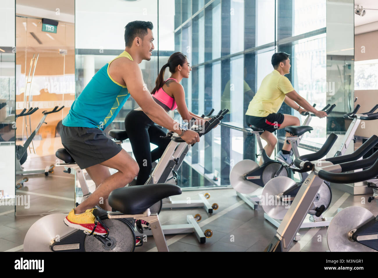 handsome and confident young man smiling while pedaling during group class of HIIT indoor cycling in a modern fitness - Stock Image