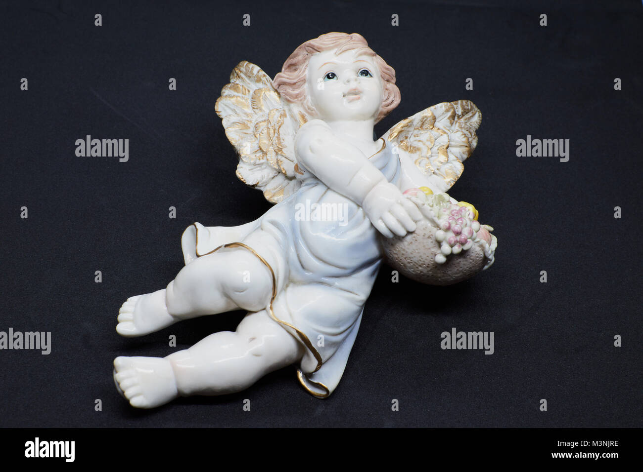 Isolated little angel with basket of fruits and blue tunic looking at the sky on black background. Closeup - Stock Image